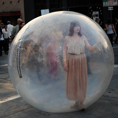 Isolation in a plastic bubble - girl in a bubble in a busy public space
