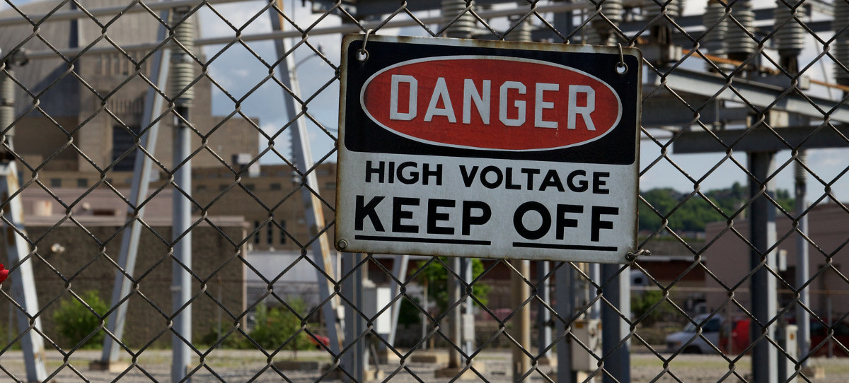 High Voltage Keep Off sign on chain link fence by electrical gear