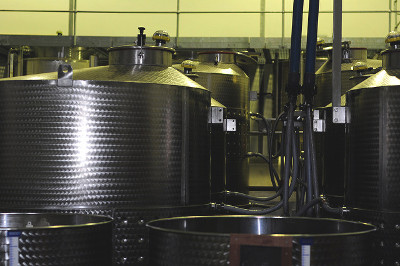Shiny stainless steel tanks in an indoor process area.