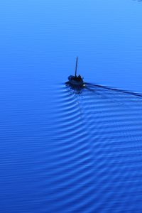 Small sail boat on calm blue water under power, leaving ripples