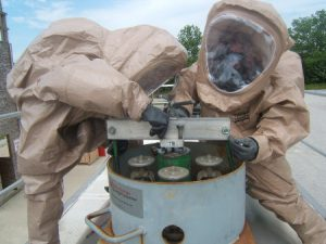 Haz-mat suited workers deal with canisters in a drum