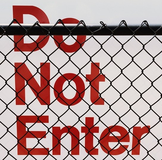 Do not enter sign behind chain link fence